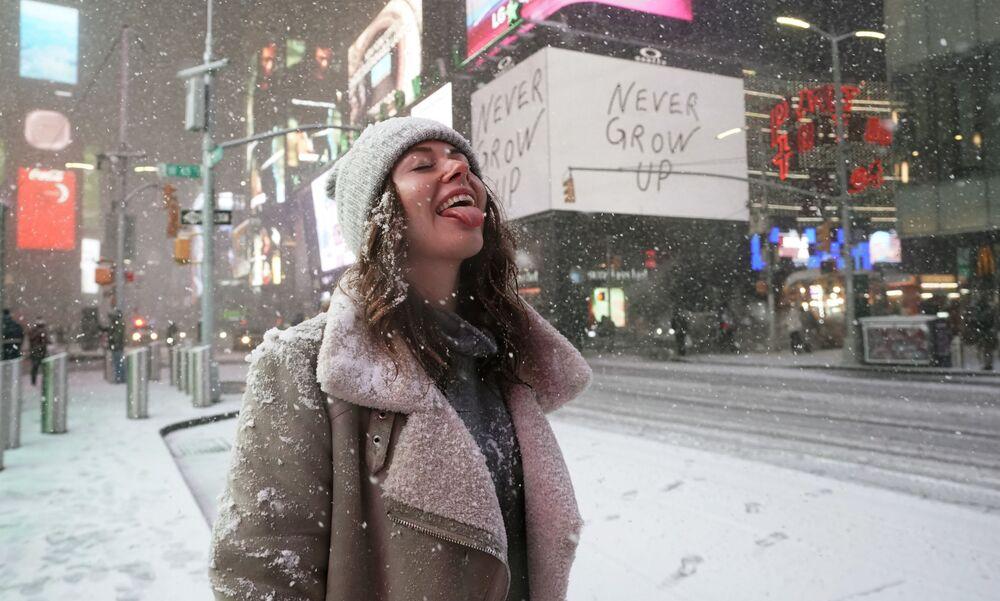Turista parada debaixo da neve em Times Square, Nova York, EUA, enquanto a tempestade Gail atinge a costa leste, 16 de dezembro de 2020