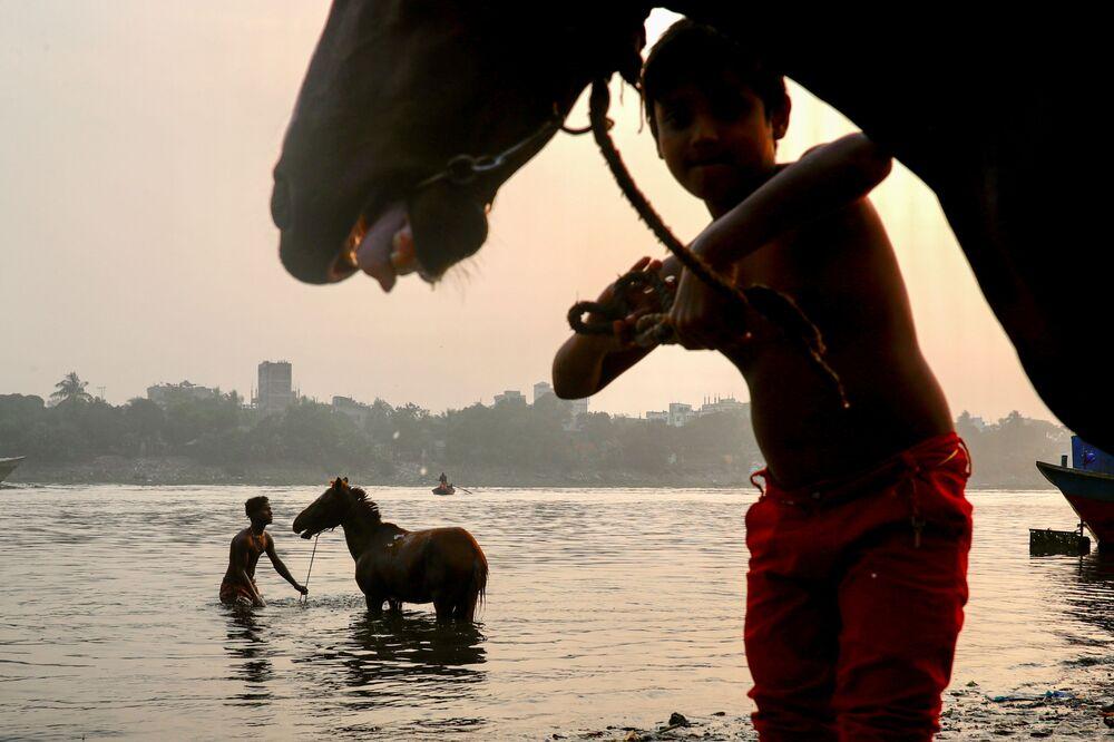 Homem banha um cavalo no rio Buriganga em Daca, Bangladesh, 15 de dezembro de 2020