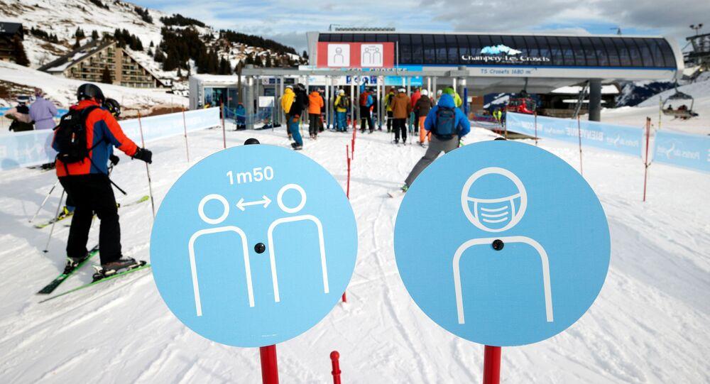 Em Les Crosets, na Suíça, esquiadores passam por placas que sinalizam medidas de proteção contra a COVID-19, em 19 de dezembro de 2020