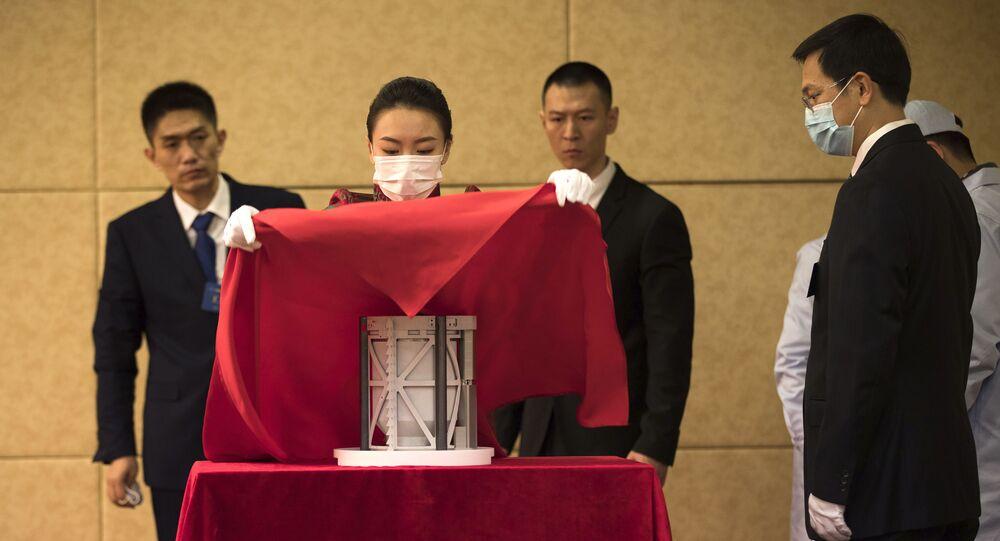 Em Pequim, na China, funcionários da Administração Espacial Nacional da China (CNSA) cobrem um compartimento contendo solo e rocha lunar coletados pela missão Chang'e-5 durante cerimônia de entrega das amostras a cientistas chineses, em 19 de dezembro de 2020