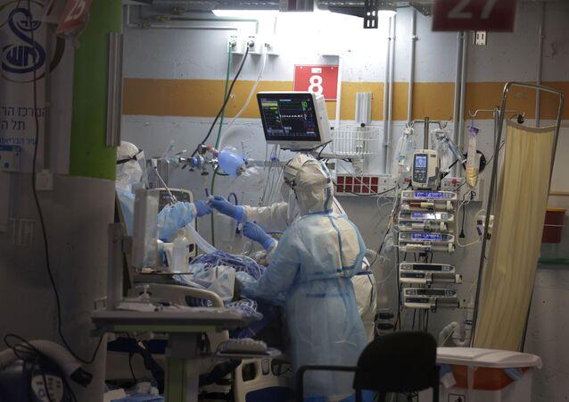 Médicos atendem um homem idoso na unidade de cuidados intensivos de coronavírus, que foi construída em uma garagem subterrânea no Sheba Medical Center, em Ramat Gan, Israel.
