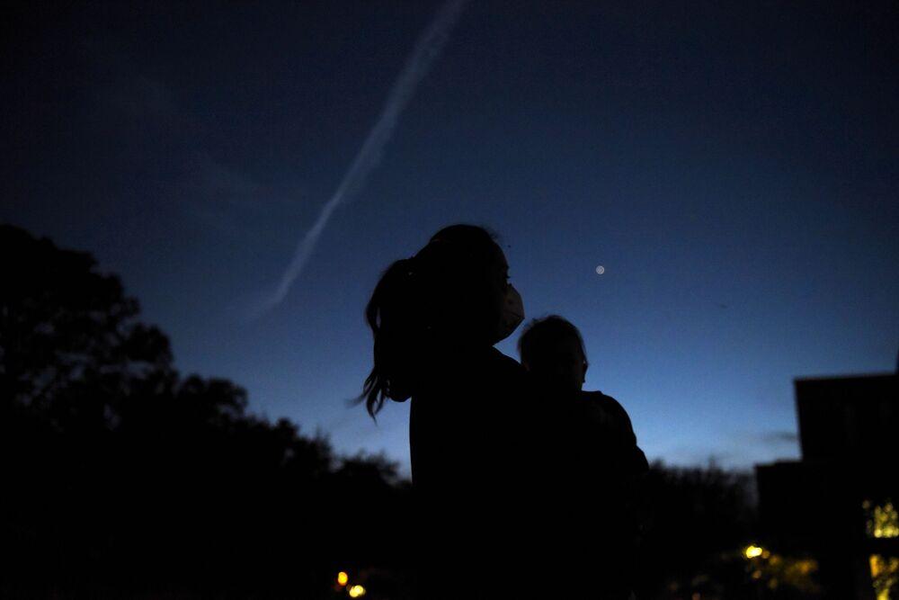 Mulher segura seu filho enquanto observam Saturno e Júpiter durante a conjunção entre os dois planetas, Texas, EUA, 21 de dezembro de 2020