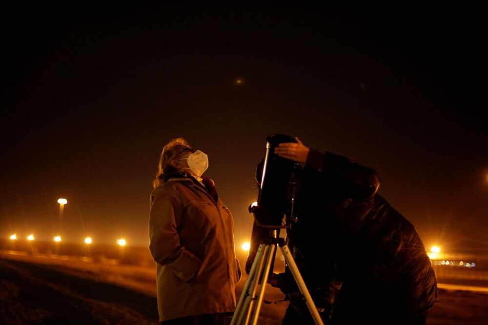Casal observa por um telescópio Saturno e Júpiter durante a conjunção planetária, na fronteira entre o México e os Estados Unidos, 21 de dezembro de 2020