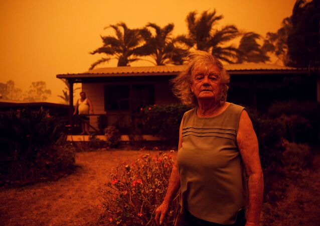Casal australiano em frente à sua residência, conforme o vento traz chamas e cinzas, durante incêndios florestais na Austrália, 4 de janeiro de 2020