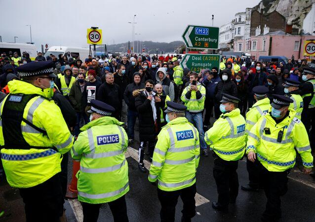 Motoristas junto de policiais bloqueando a saída no Porto de Dover, Reino Unido, durante a proibição de viagens do Reino Unido devido a uma nova estirpe do coronavírus, em 23 de dezembro de 2020