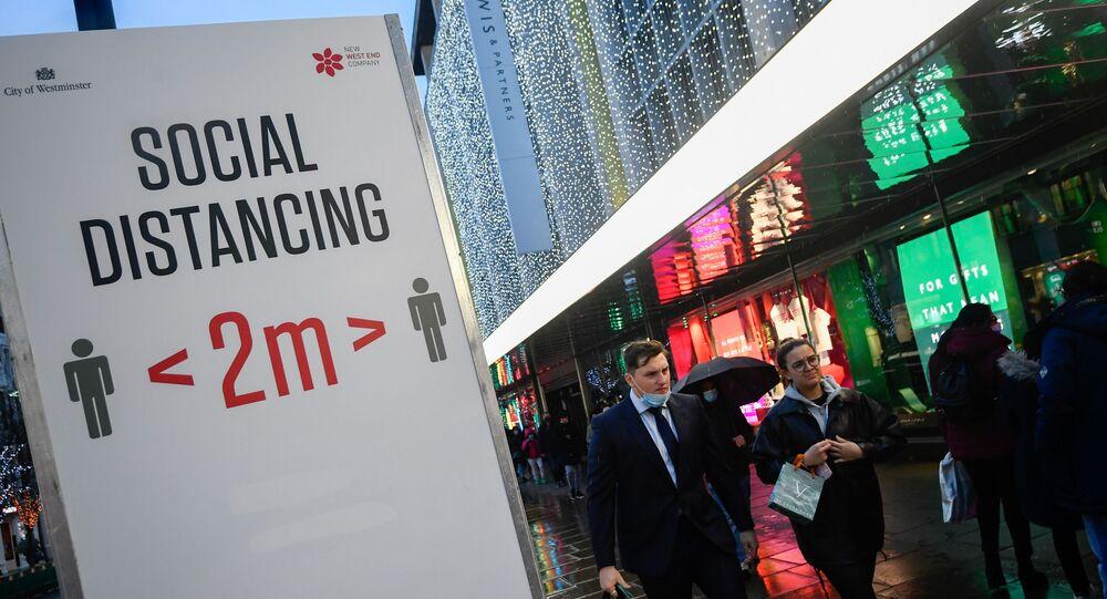 Compradores passam por um sinal de distanciamento social em meio à pandemia da doença do coronavírus (COVID-19) em Londres, Reino Unido, 16 de dezembro de 2020