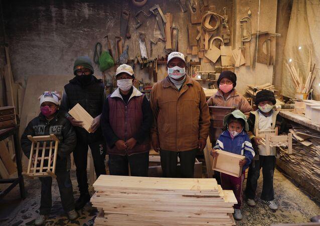 Família usa máscara em sua carpintaria, em El Alto, Bolívia, 29 de agosto de 2020