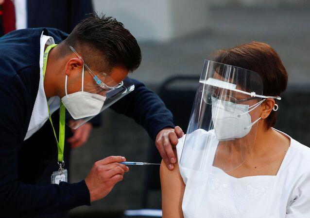 Maria Irene Ramirez, de 59 anos, recebe a primeira vacina contra a COVID-19 do México, na Cidade do México, no dia 24 de dezembro de 2020.