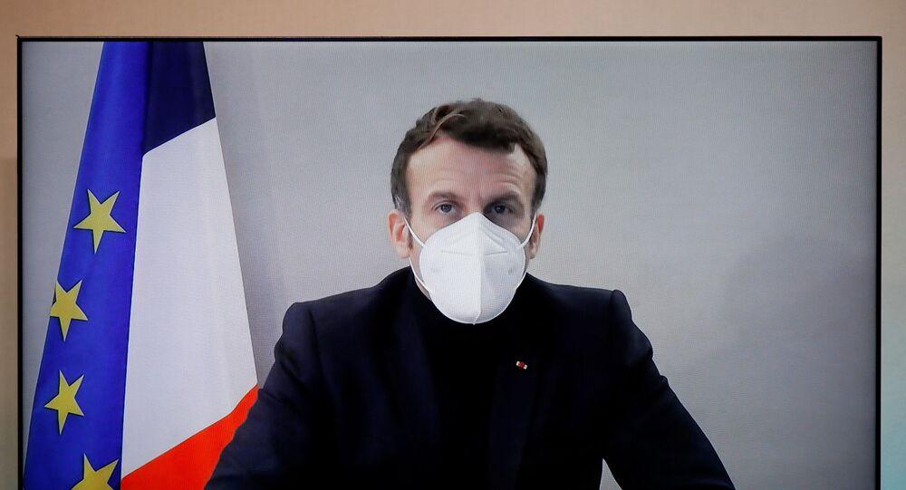 O presidente da França, Emmanuel Macron, com teste positivo para COVID-19, é visto em uma tela enquanto participa por videoconferência de uma mesa redonda da Conferência Humanitária Nacional (NHC)