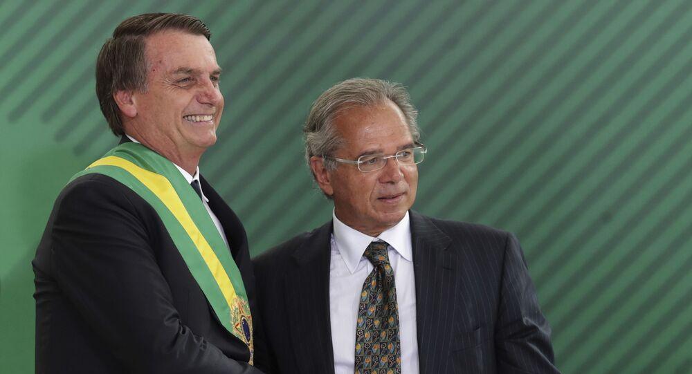 Presidente do Brasil, Jair Bolsonaro aperta a mão do ministro da Economia, Paulo Guedes, durante cerimônia de posse ministerial