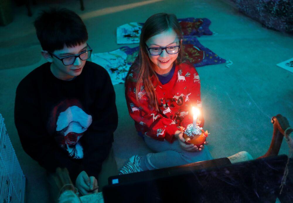 Crianças durante transmissão on-line do Christingle na véspera de Natal, Blakesley, Reino Unido, 24 de dezembro de 2020