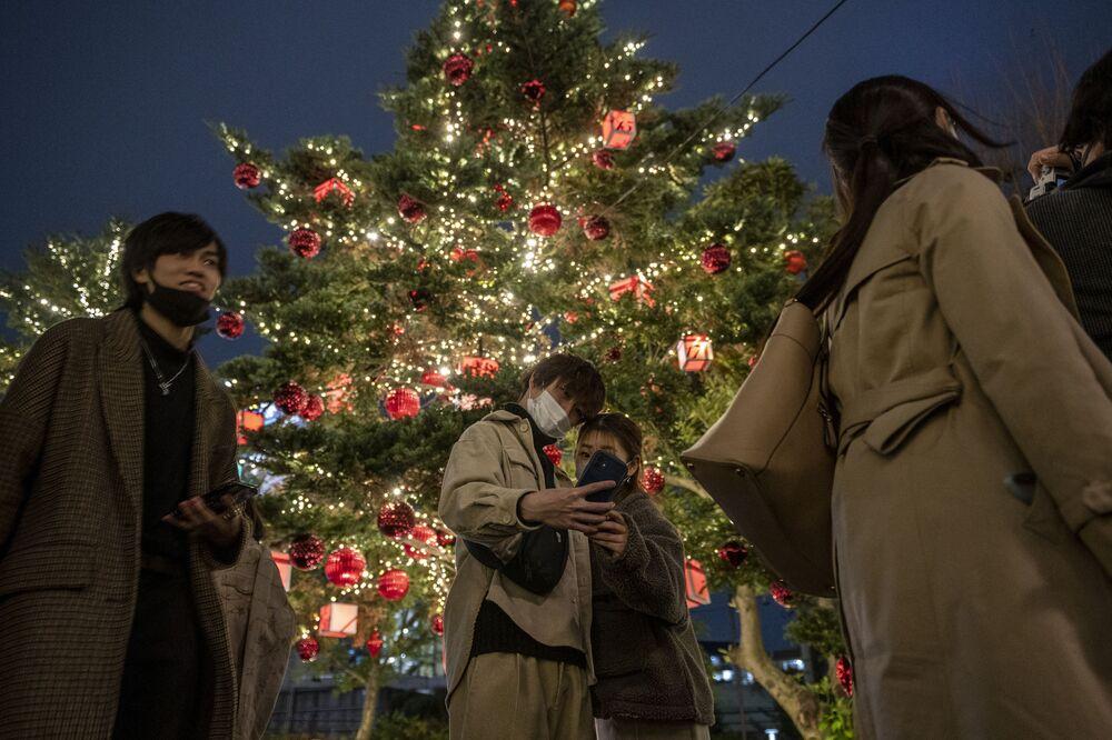 Casal tira selfie com árvore de Natal em Tóquio, Japão, 24 de dezembro de 2020