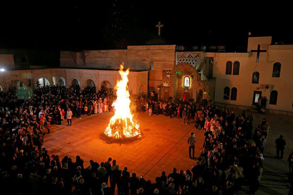 Cristãos iraquianos se reúnem em torno de fogueira durante missa de Natal em Hemdaniye, Iraque, 24 de dezembro de 2020