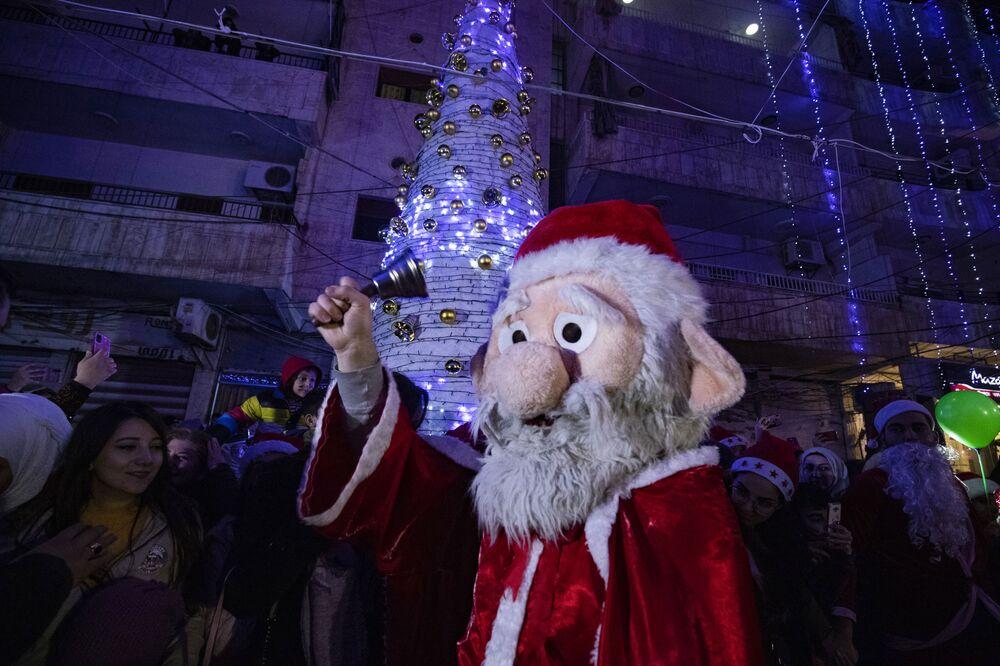 Homem fantasiado de Papai Noel em Qamishli, Síria, 24 de dezembro de 2020