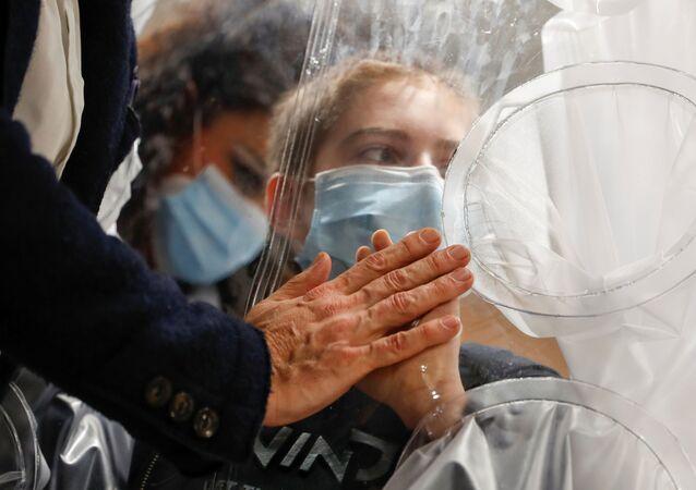 Menino hospitalizado infectado com COVID-19 toca a mão de seu pai através de proteção de plástico no hospital de San Raffaele em Roma, Itália, 22 de dezembro de 2020