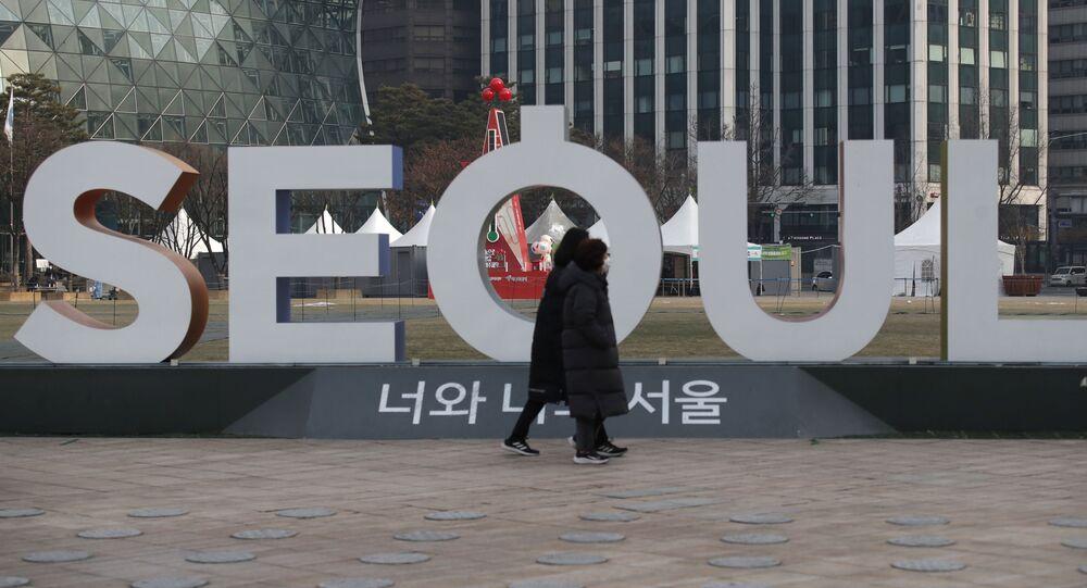 Mulheres usando máscaras faciais como precaução contra o coronavírus caminham perto da exibição do logotipo da capital da Coreia do Sul, Seul