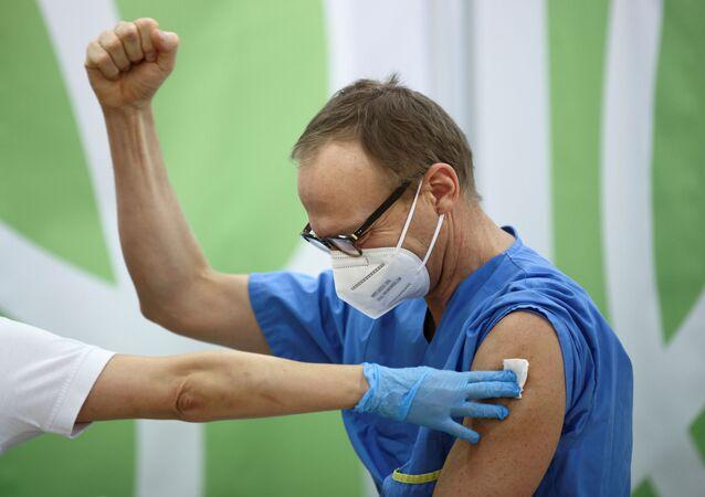 Agente de saúde reage após receber primeira dose de vacina contra COVID-19, em Viena, Áustria, 27 de dezembro de 2020