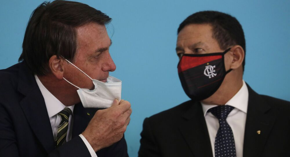 O presidente Jair Bolsonaro e o vice-presidente Hamilton Mourão conversam durante evento no Palácio do Planalto.