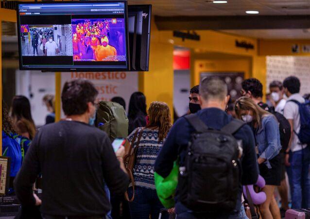 Passageiros passam por scanner de temperatura, no aeroporto de Guarulhos, São Paulo, 27 de dezembro de 2020