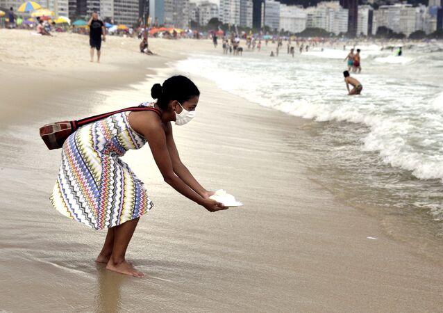 Mulher faz oferendas à Iemanjá na praia de Copacabana, Rio de Janeiro, 29 de dezembro de 2020