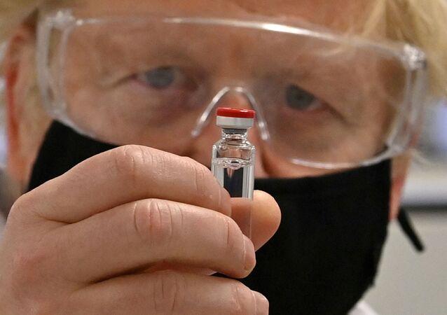 Primeiro-ministro britânico, Boris Johnson, segura ampola de vacina da AstraZeneca/Oxford (foto de arquivo)