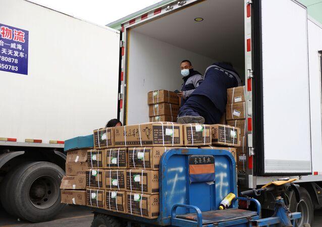 Trabalhadores transportam produtos de carne congelada em um caminhão durante a pandemia do novo coronavírus em Pequim, China, 26 de novembro de 2020