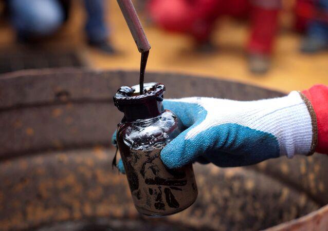 Trabalhador coleta uma amostra de petróleo bruto em um poço de petróleo operado pela estatal venezuelana PDVSA em Morichal, na Venezuela