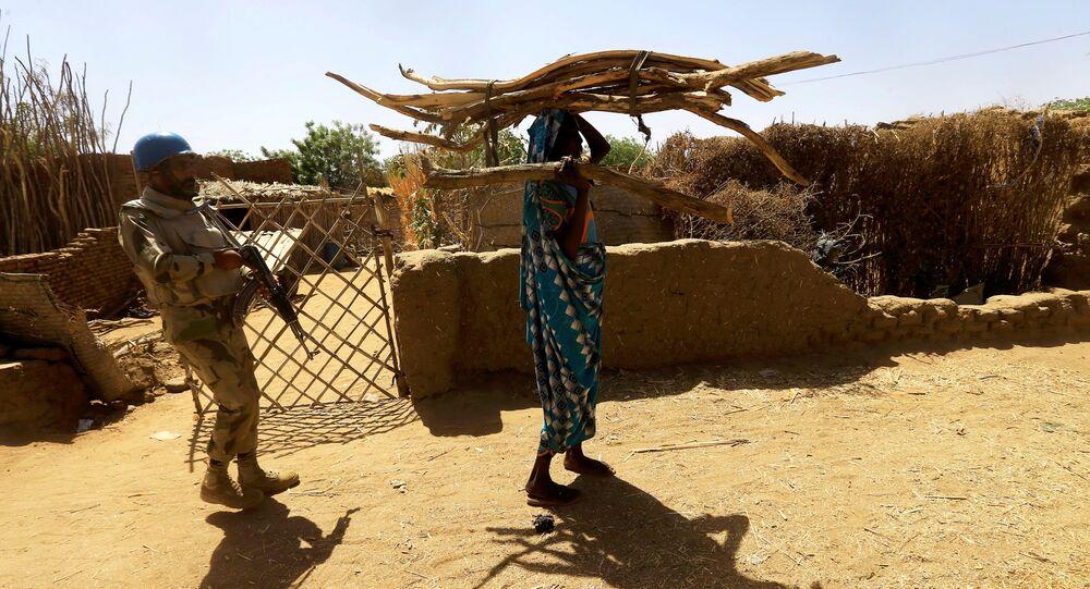 Um pacificador da Operação Híbrida das Nações Unidas em Darfur (UNAMID) acompanha uma mulher sudanesa carregando lenha na cabeça enquanto ela caminha pelo campo de Kalma para pessoas deslocadas internamente em Darfur, Sudão