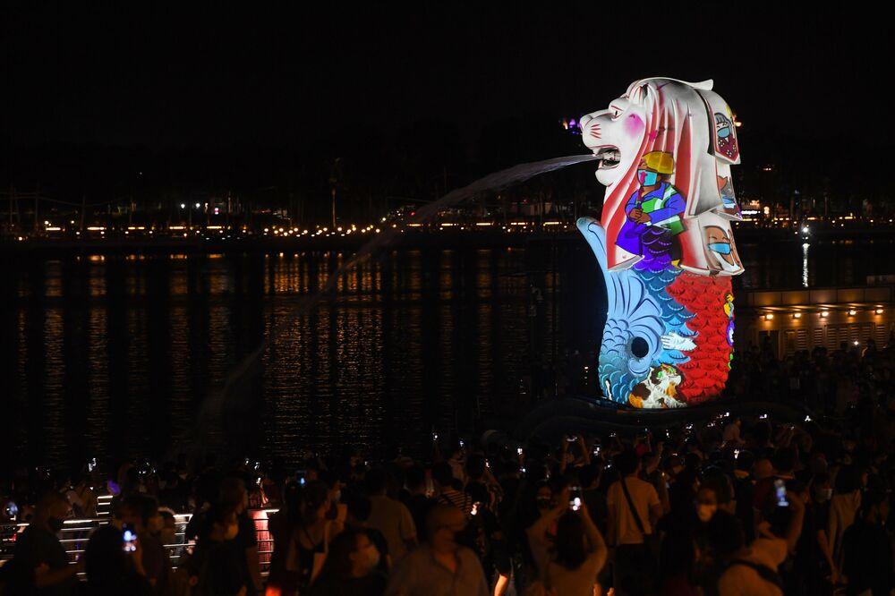 Pessoas assistem a iluminação especial da estátua do Merlion como parte das celebrações da véspera de Ano Novo em Cingapura, em 31 de dezembro de 2020