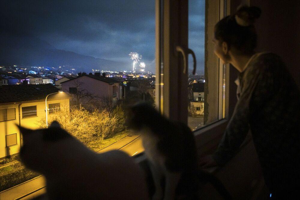 Mulher e seus gatos acompanham os fogos de artifício durante o Réveillon através da janela de casa, em Ajdovscina, Eslovênia