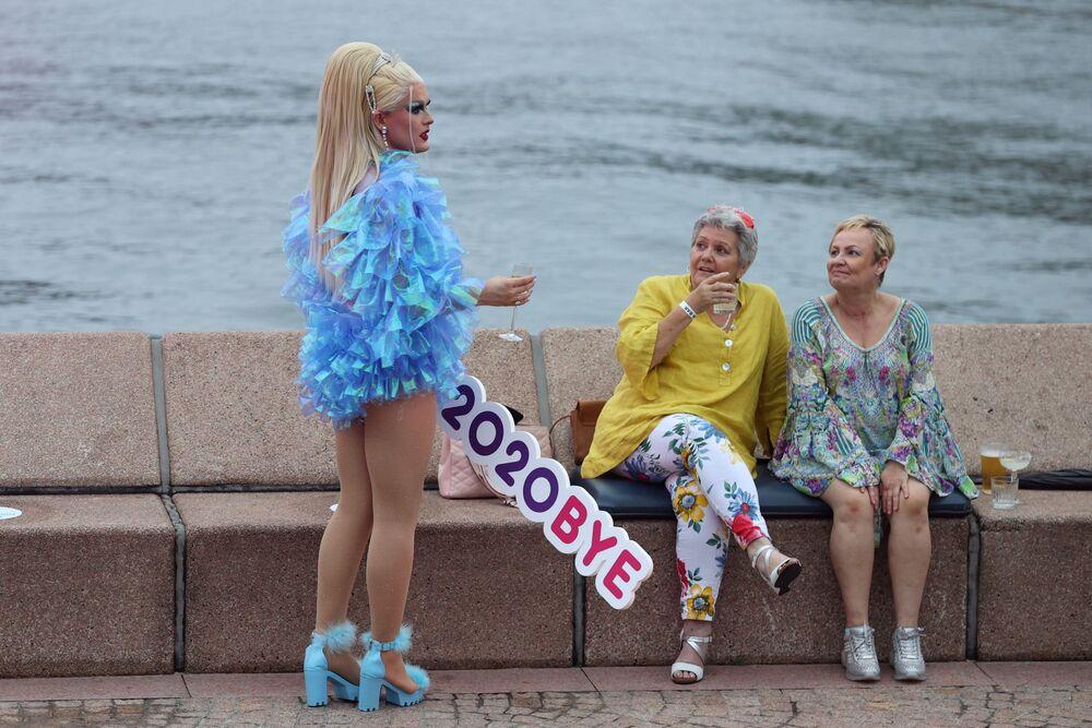 Foliã segura uma placa que diz Tchau 2020 durante a véspera de Ano Novo na orla de Sydney, Austrália