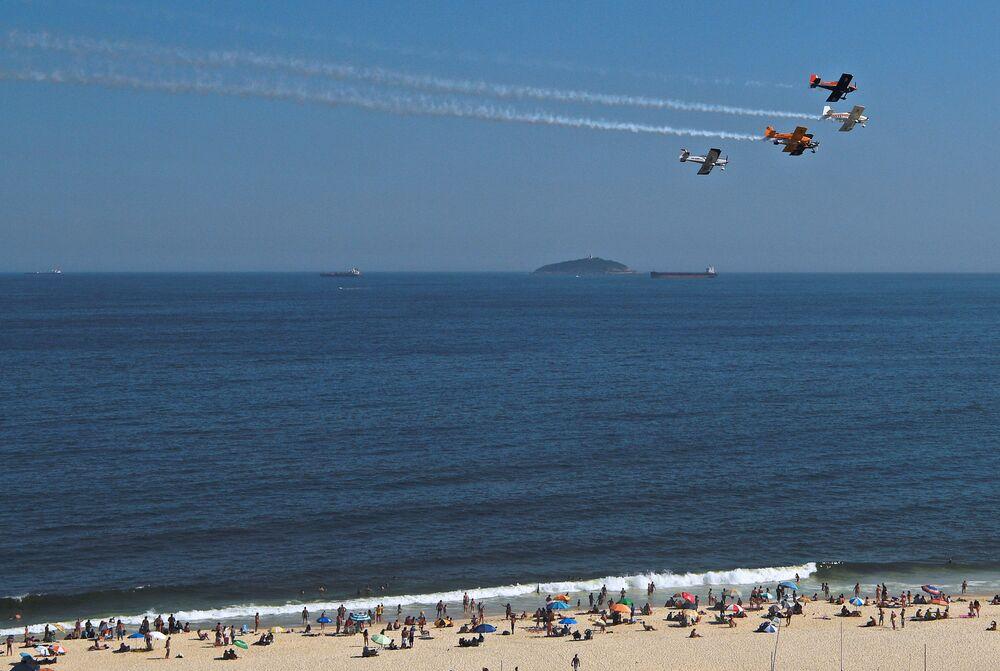 Aviões realizam manobras aéreas deixando rastros de fumaça e entretendo banhistas na praia de Copacabana, Rio de Janeiro, Brasil, em 31 de dezembro de 2020