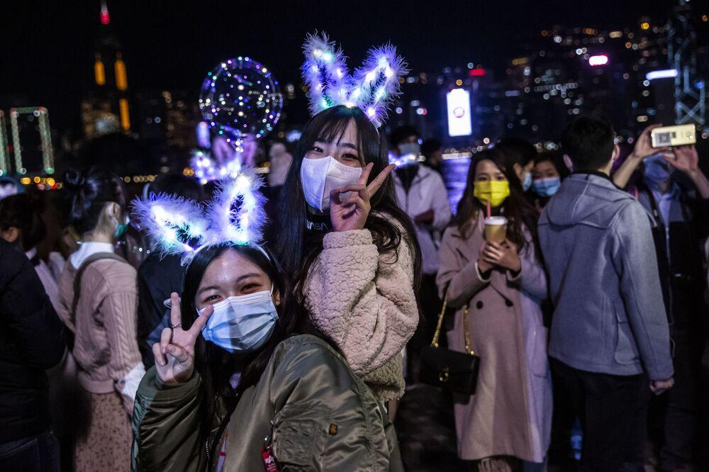 Duas jovens posam perto da orla marítima de Hong Kong, em 1º de janeiro de 2021. Apesar das restrições devido à pandemia de COVID-19, as pessoas se reuniram para celebrar o Ano Novo