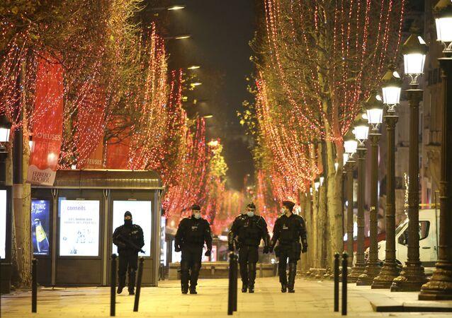 Policiais patrulham a avenida Champs Elysées durante a véspera de Ano Novo. A França implementou uma toque de recolher das 20h00 às 6h00 para evitar uma terceira onda de infecções de COVID-19