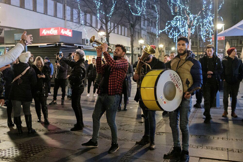 Pessoas tocam, cantam e dançam nas ruas de Belgrado, Sérvia, após o Ano Novo chegar