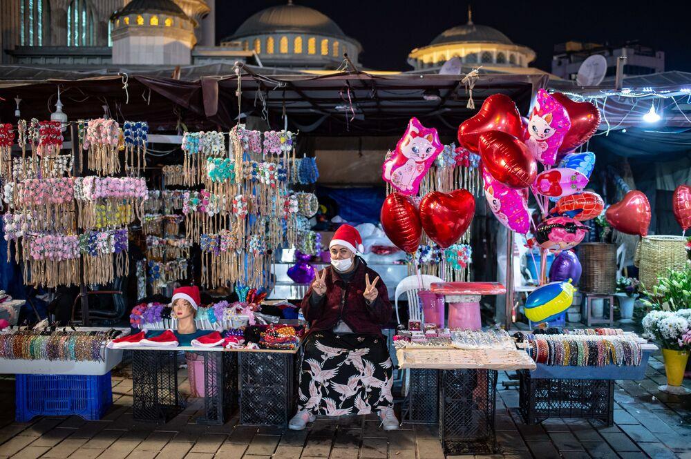 Vendedora de rua faz o V de vitória na praça Taksim, Istambul, Turquia, durante as celebrações do Réveillon, em 31 de dezembro de 2020