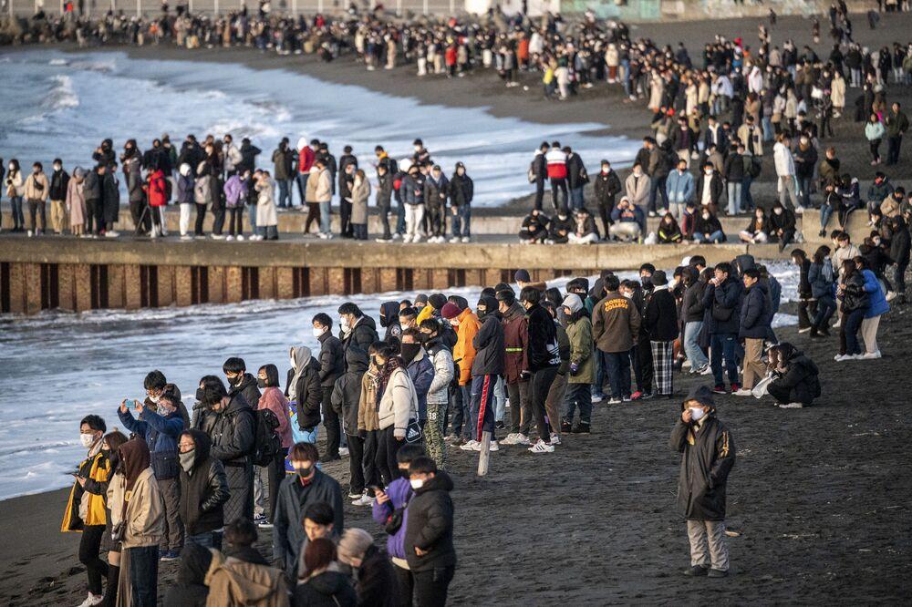 Pessoas se reúnem em praia para assistir ao nascer do sol no dia de Ano Novo na província de Kanagawa, a sudoeste de Tóquio, Japão, em 1º de janeiro de 2021