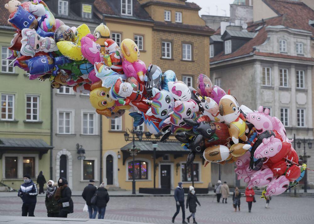 Vendedor de balões espera por clientes na geralmente movimentada praça do Castelo, em Varsóvia, Polônia, que agora tem poucas pessoas por causa das restrições para conter o avanço da COVID-19, em 31 de dezembro de 2020