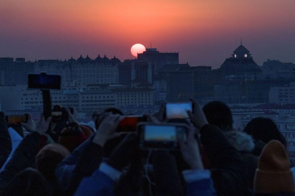 Pessoas tiram fotos no primeiro nascer do sol de 2021, em Pequim, China, em 1º de janeiro de 2021