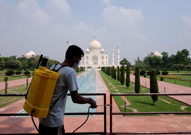 Funcionário de saúde higieniza corrimões tendo ao fundo o palácio Taj Mahal que foi reaberto em setembro de 2020