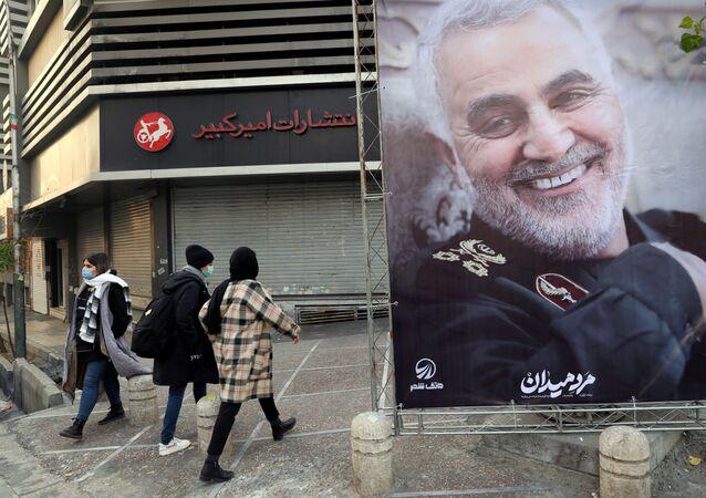 Pessoas caminham perto de pôster do general Qassem Soleimani, militar iraniano sênior, exposto pelo aniversário de um ano de sua morte por ataque dos EUA, em Teerã, Irã, 1º de janeiro de 2021