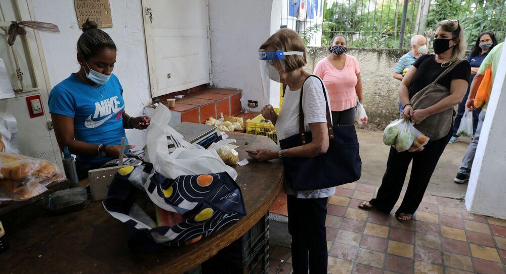 Pessoas usando máscaras contra coronavírus fazem compra em mercado aberto em Caracas, na Venezuela