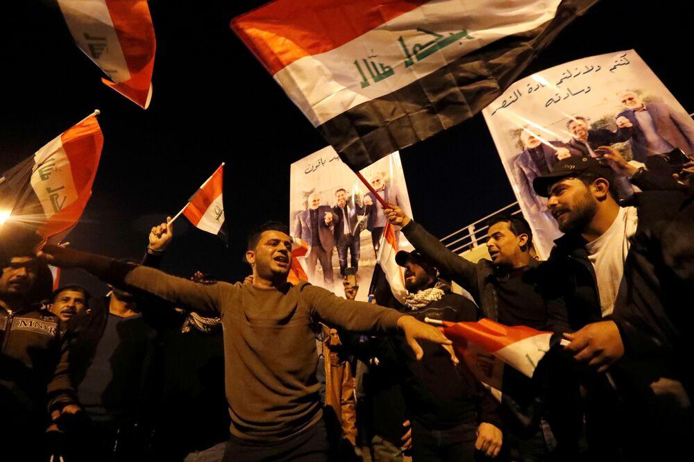 Iraquianos levantam bandeiras do Irã e pôsteres do major-general iraniano Qassem Soleimani e do líder da milícia xiita iraquiana Abu Mahdi al-Muhandis