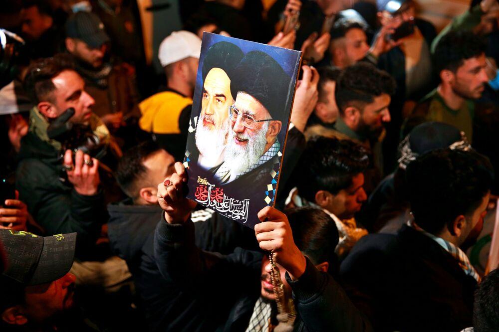 Membros das Forças de Mobilização Popular xiitas do Iraque cantam slogans contra os EUA no Aeroporto Internacional de Bagdá, Iraque, ao passo que homenageiam o major-general iraniano Qassem Soleimani