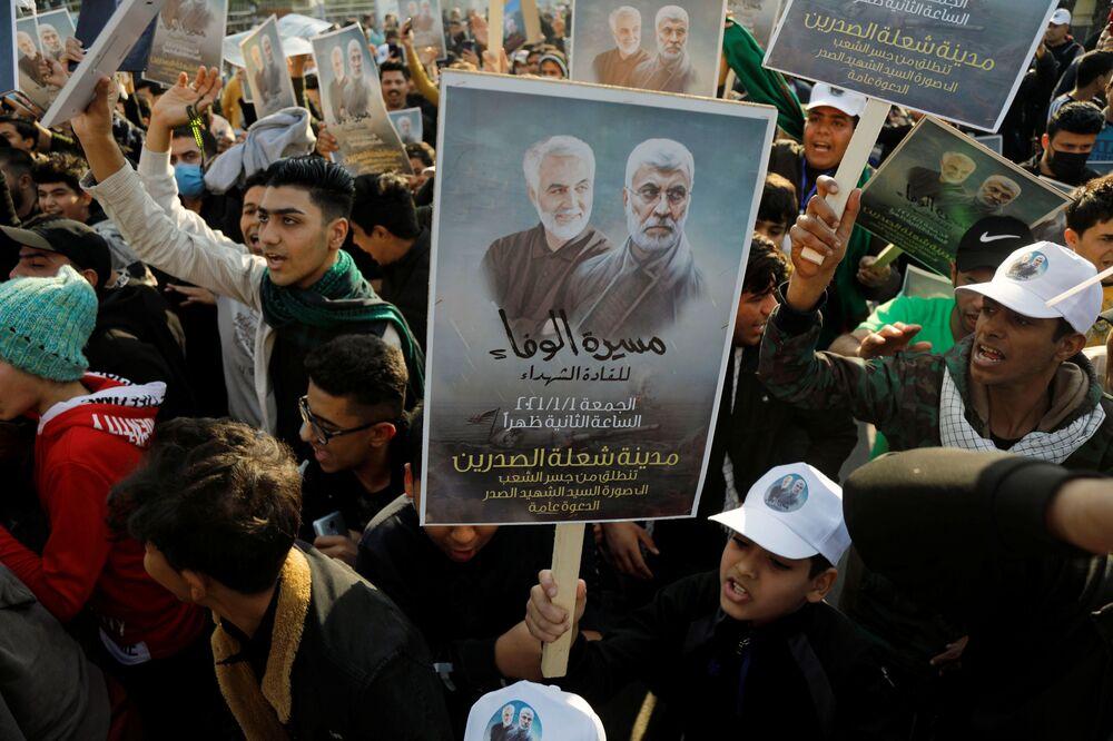 Cidadãos iraquianos carregam foto do major-general iraniano Qassem Soleimani e do líder da milícia xiita iraquiana Abu Mahdi al-Muhandis