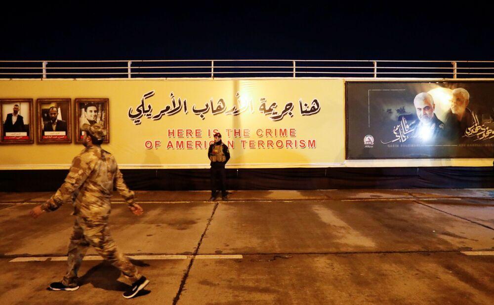 Combatente das Forças de Mobilização Popular xiitas do Iraque fica em pé tendo ao fundo imagens do major-general iraniano Qassem Soleimani e do líder da milícia xiita iraquiana Abu Mahdi al-Muhandis