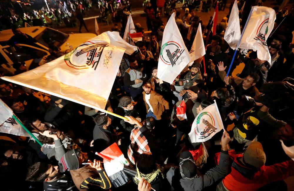 Pessoas levantam bandeiras durante o primeiro aniversário da morte do major-general iraniano Qassem Soleimani e do líder da milícia xiita iraquiana Abu Mahdi al-Muhandis em Bagdá, Iraque