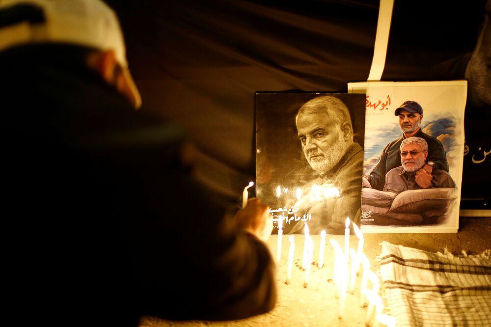 Vela é posta perto dos retratos do major-general iraniano Qassem Soleimani e do líder da milícia xiita iraquiana Abu Mahdi al-Muhandis em ato de um ano do aniversário da morte de ambos durante operação dos EUA, Bagdá, Iraque