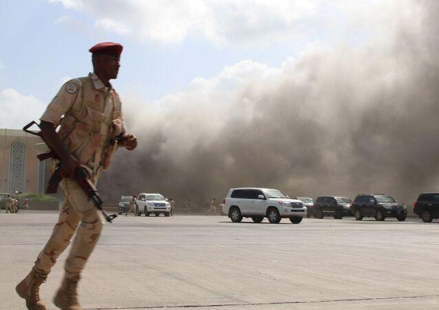 Agente de segurança corre durante ataque no Aeroporto Internacional de Aden, no Iêmen.