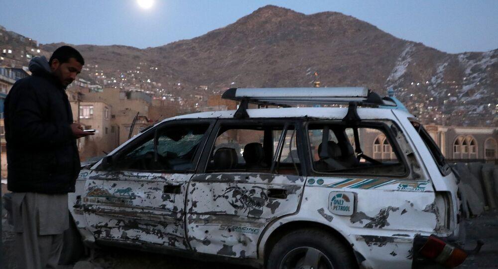 Um afegão inspeciona carro danificado após a explosão de uma bomba em Cabul, Afeganistão